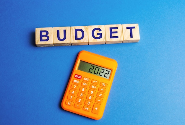 Wooden blocks with the word budget and a calculator with numbers 2022