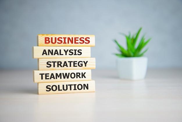 ワードビジネス、分析戦略チームワークソリューションを備えた木製のブロック。ビジネスコンセプトの背景。