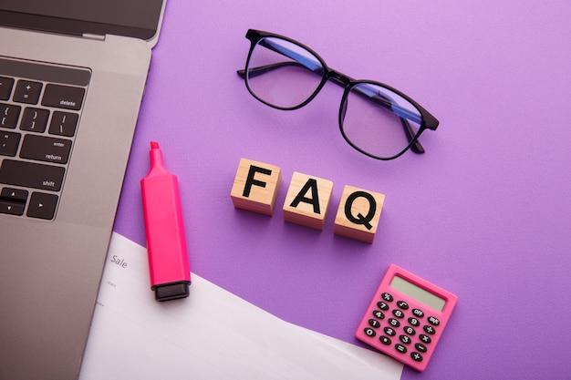 Деревянные блоки со словом faq на розовом столе. часто задаваемый вопрос