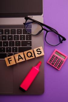 ピンクのテーブルにfaqという言葉が書かれた木製のブロック。よくある質問。垂直方向の画像。
