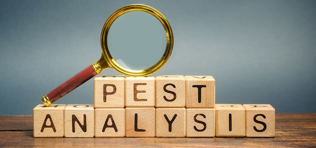 Wooden blocks with the word pest analysis and a magnifying glass. political, economic