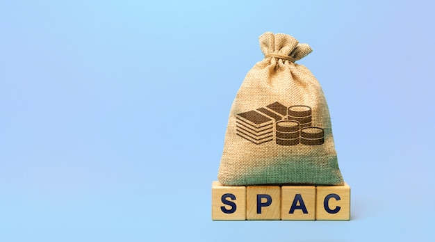 Wooden blocks with the word spac and money bag  special purpose acquisition company