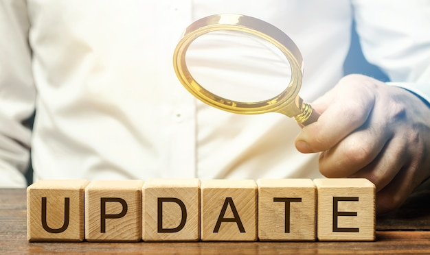 Wooden blocks with the word update and a magnifying glass. updating the version