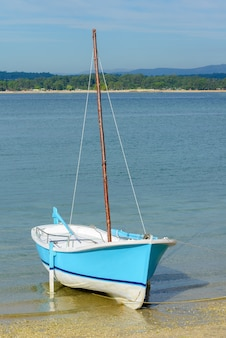 Wooden blue fishing sailboat anchored near the shore