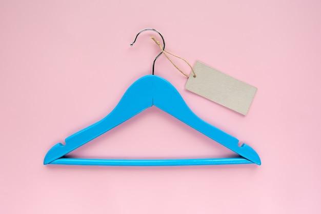 ピンクの紙の背景に分離された黒い紙ラベルと木製の青いハンガー。衣類タグ、ラベルbla