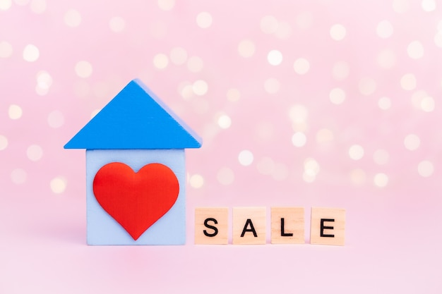 Wooden blue house with red heart and with text sale on pink bokeh wall with copy-space. concept rental, construction and home buying, purchase and discounts.