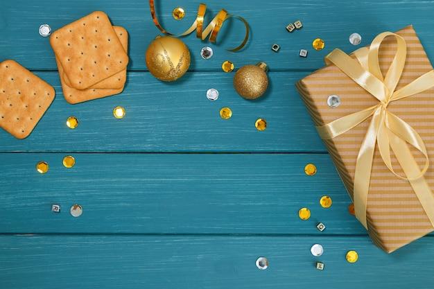 Деревянная синяя поверхность и золотые рождественские украшения и подарки