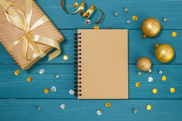 Деревянная синяя поверхность с золотыми рождественскими украшениями, блокнотом и подарочной коробкой