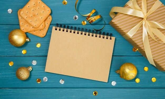 Деревянная синяя поверхность с золотыми елочными украшениями, блокнотом, крекерами и подарочной коробкой