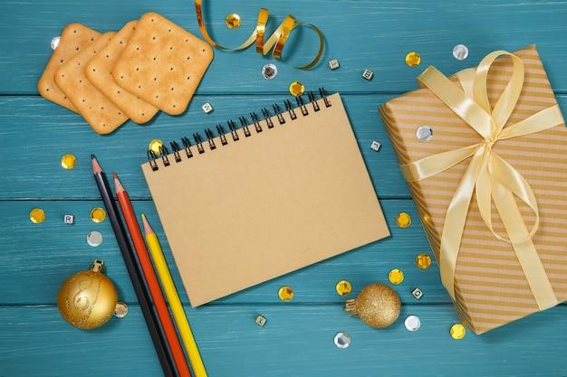 Деревянная синяя поверхность с золотыми рождественскими украшениями, карандашами, крекерами и подарками
