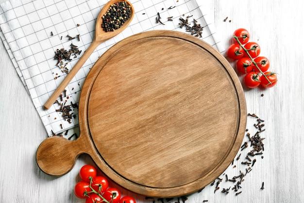 Деревянная доска и помидоры со специями на кухонном столе.