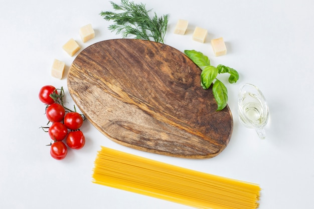 Wooden board, around it are tomatoes, olive oil, dill, cheese, basil and spaghetti pasta