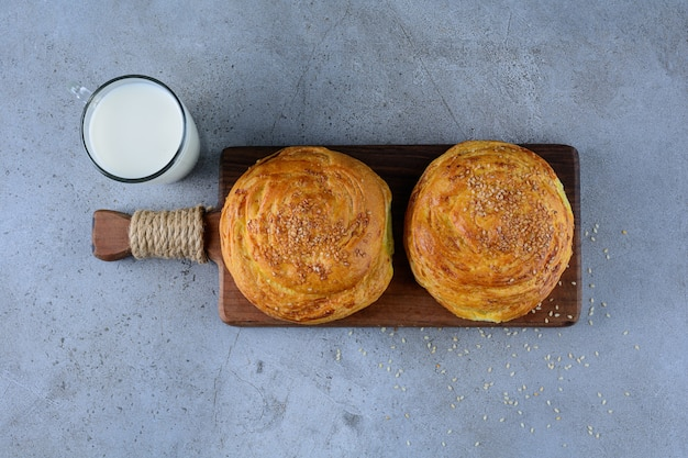 A wooden board of azerbaijan national pastry with a glass cup of fresh milk .