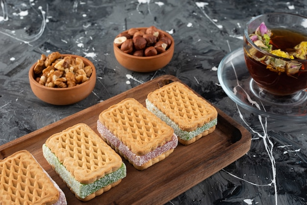 A wooden board of belqian waffles with a cup of tea and healthy nuts