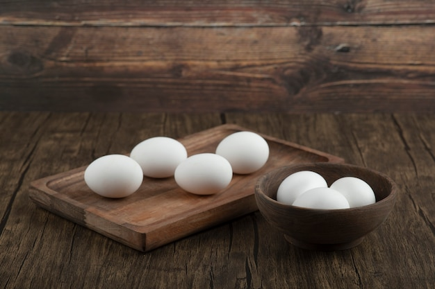 Wooden board and bowl full of organic raw eggs on wooden background.