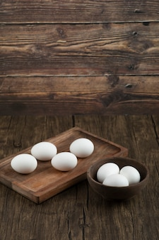Wooden board and bowl full of organic raw eggs on wooden surface.