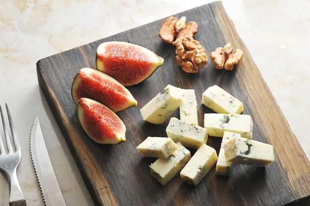 On a wooden board, cheese with blue mold dorblu, a few figs and walnuts.