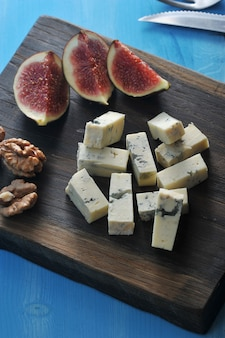 On a wooden board, cheese with blue mold, a few figs and walnuts.
