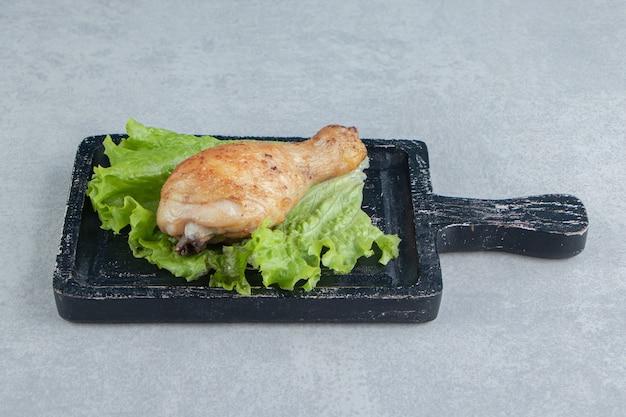 Una tavola di legno di coscia di pollo fritta con lattuga.