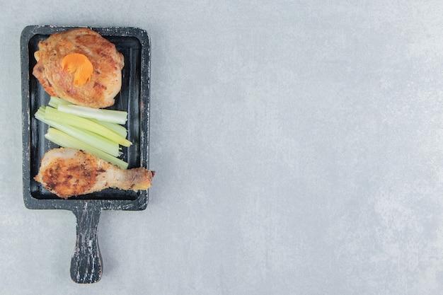 A wooden board of chicken fried meat .