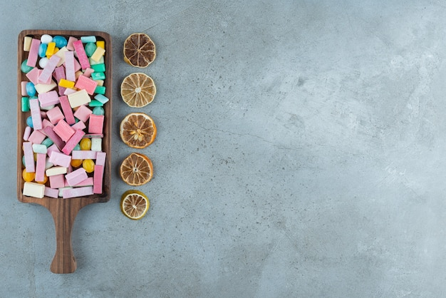 Wooden board of colorful bubble gums and lemon slices on stone.