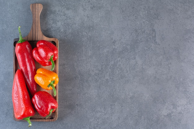 Wooden board of colorful fresh bell peppers on stone background.