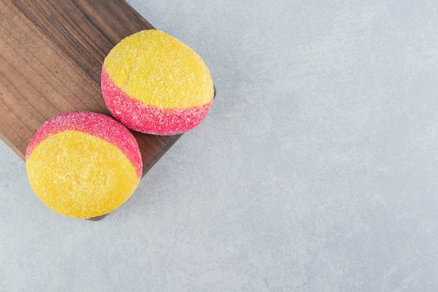 A wooden board of colorful sweet cookies .