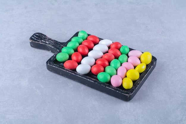 Una tavola di legno di caramelle colorate di fagioli di gelatina dolce. foto di alta qualità