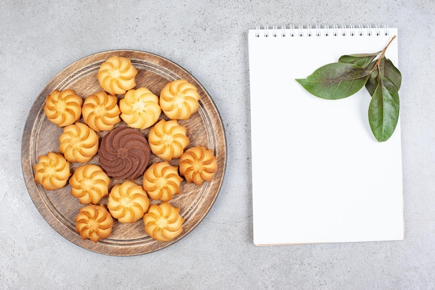 A wooden board of cookies next to a notebook with leaves on marble background.