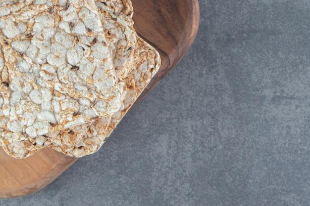 Una tavola di legno di cialde di riso quadrati croccanti.