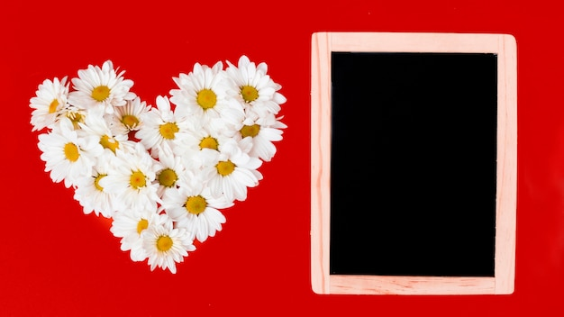 Wooden board and daisy flowers in heart shape