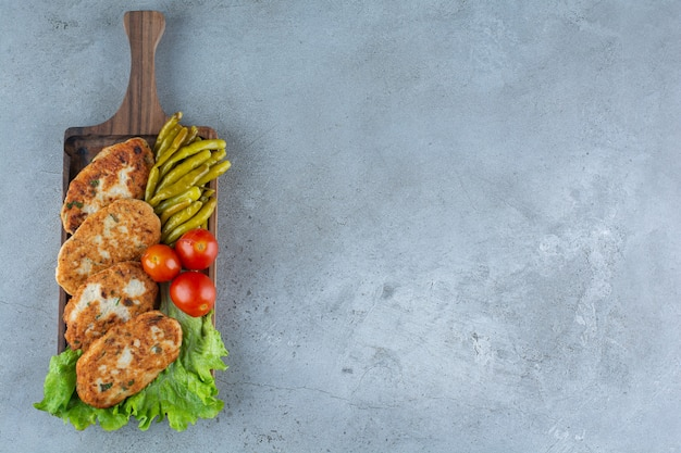 Wooden board of delicious chicken cutlets on stone surface.