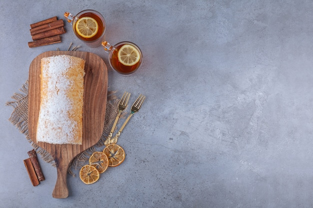 Wooden board of delicious sponge cake with cups of tea on marble background.