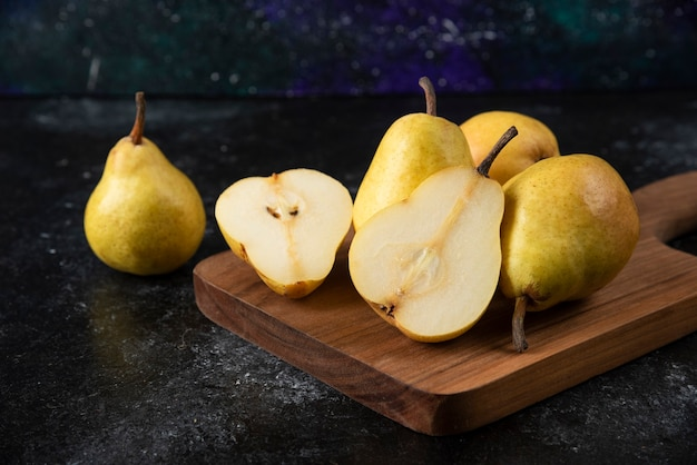 Wooden board of delicious yellow pears on black surface.