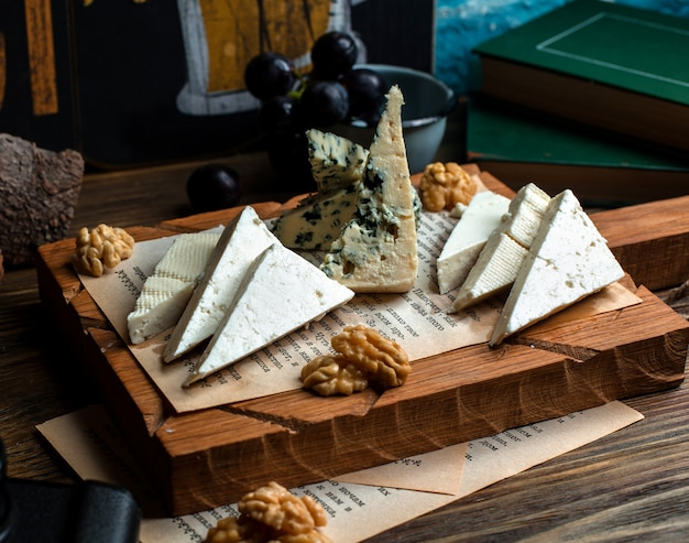 Wooden board of different cheeses and walnuts