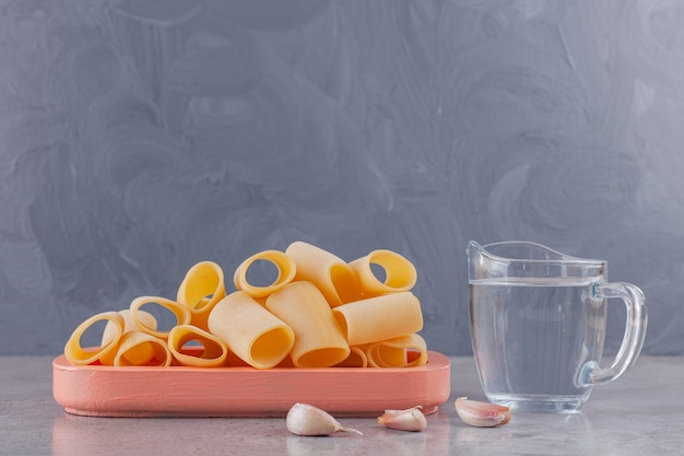 A wooden board of dry raw tube pasta with fresh cloves of garlic and a glass pitcher of water .