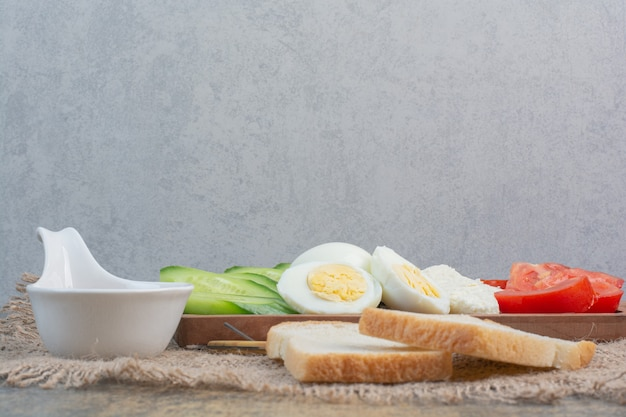 Wooden board of eggs, cheese and vegetables with bread.