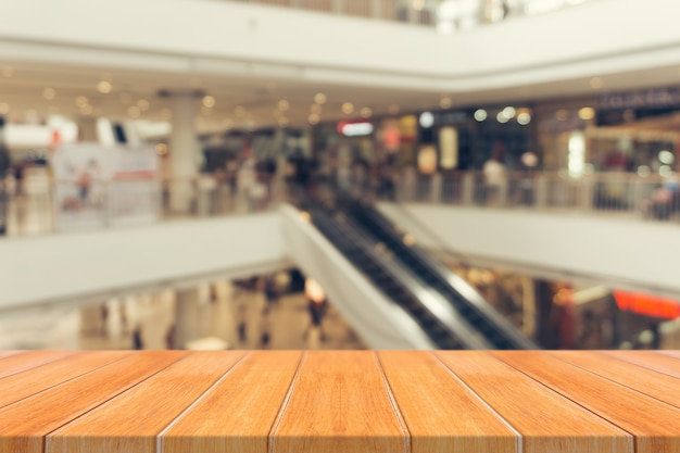 Wooden board empty table blur in department store background.