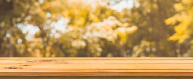 Деревянная доска пустой стол размывает деревья фоне леса.