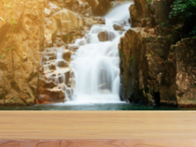 Wooden board empty table blur waterfall in forest background.