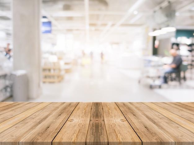 木製のボードの空の表ショッピングモールの背景をぼかした。百貨店のバックグラウンドで見える茶色の木製テーブルのぼかしが展示されています。製品のためにモックアップ