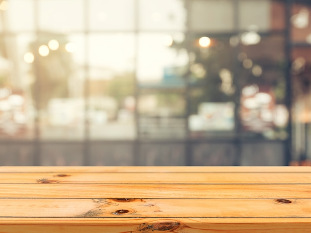 Wooden board empty table in front of blurred coffee shop background.