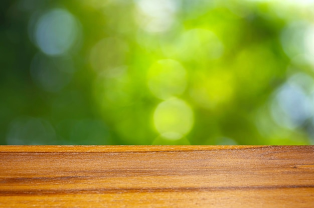Wooden board empty table in front of green bokeh background for display of product