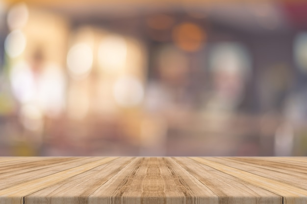 Wooden board empty table in front of in restaurant blurred background.