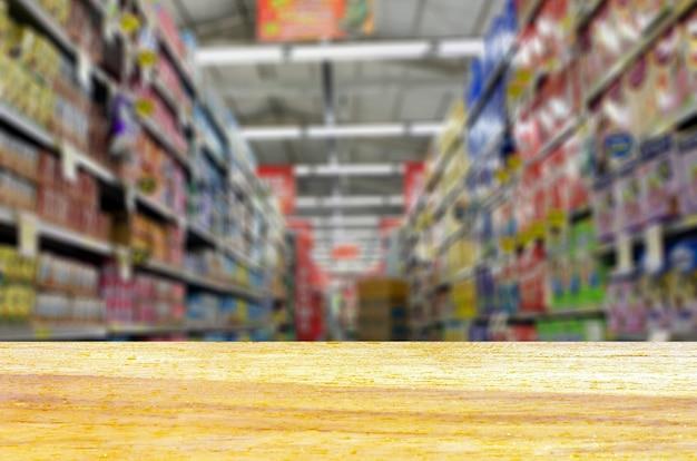 空のぼかしスーパーマーケットの通路の前にある木の板の空のテーブル