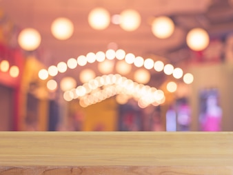 ぼんやりした背景の前に木製ボードの空のテーブル。コーヒーショップでのぼかしの上に見える茶色の木