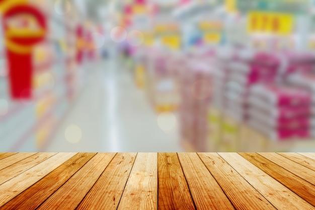 배경 흐리게 앞 나무 보드 빈 테이블. 슈퍼마켓에서 흐림 효과가있는 전망 가벼운 나무-디스플레이에 사용하거나 제품을 몽타주 할 수 있습니다. 제품 표시를 위해 조롱하십시오.