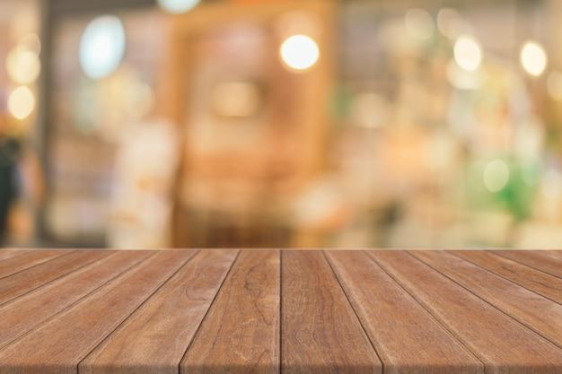 ぼやけているコーヒーショップの背景の前に木の板の空のテーブル。