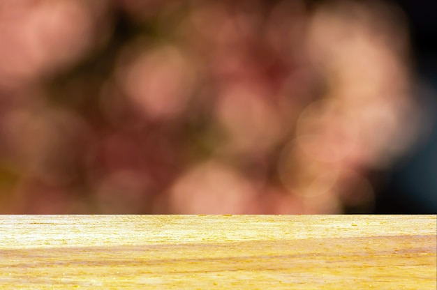 ピンクのボケ味の抽象的な背景の前に木の板の空のテーブル