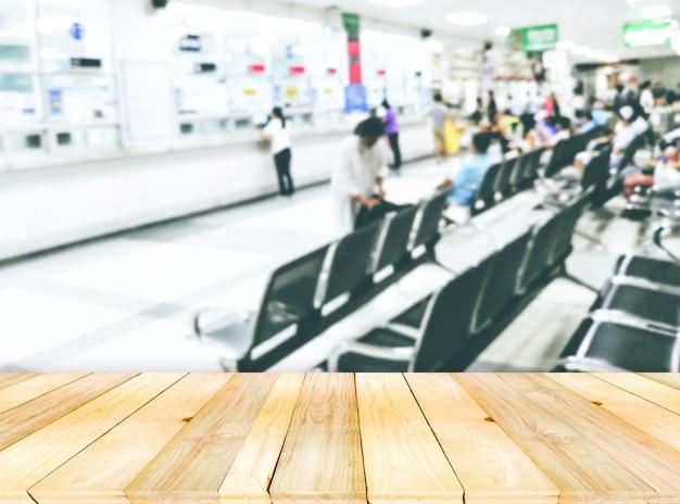 Деревянная доска пустой стол на фронте с расплывчатым множеством аномальных ожидающих лекарств толпы у рецептора лекарств в больнице.